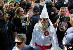 FILE - A KKK white supremacist is escorted by police during a KKK and counter-rally in Charlottesville, Virginia, July 8, 2017.