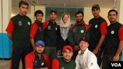 سارا فېن د افغانستان د کرېکټ د ملي لوبډلې د لوبغاړو په منځ کې ولاړه ده.