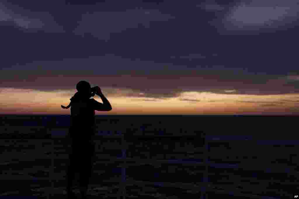 A member of SOS Mediterranee's Search and Rescue team monitors the horizon at dawn with binoculars for potential boats in distress from aboard the Ocean Viking in international waters north of Libya.