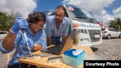 Jaqueline Goes de Jesus (Fundacao Oswaldo Cruz, Salvador), left, and Nuno Faria (University of Oxford, UK) use the Oxford Nanopore MinION device in front of the minibus equipped with a lab, in Joao Pessoa, Brazil. (Courtesy - Ricardo Funari)