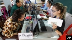 Locals, left, sit for registering their names during a voter registration process of the National Election Committee (NEC) in Phnom Penh, Cambodia, Thursday, Sept. 1, 2016. NEC started its three-month-long voter registration in the day for the next general election scheduled for July 2018. (AP Photo/Heng Sinith)