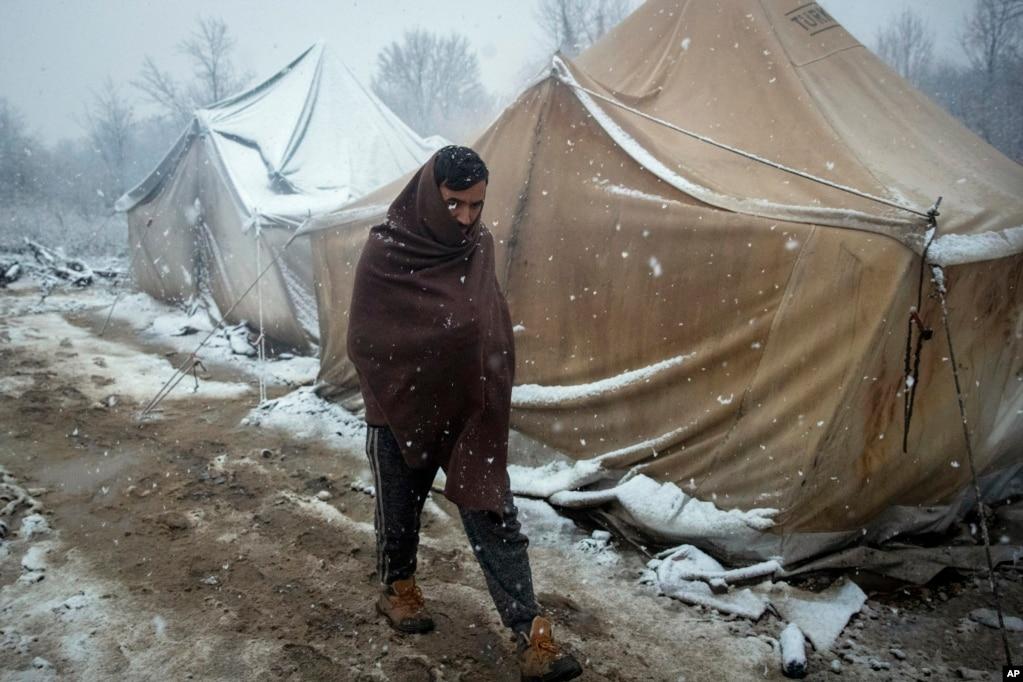 A migrant walks as snow falls at the Vucjak refugee camp outside Bihac, northwestern Bosnia.