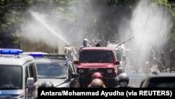 Petugas Satgas COVID-19 mengenakan alat pelindung diri (APD) menyemprotkan disinfektan di jalan untuk mencegah penyebaran COVID-19 di Solo, Jawa Tengah, 6 Juli 2021. (Foto: Antara/Mohammad Ayudha via Reuters)