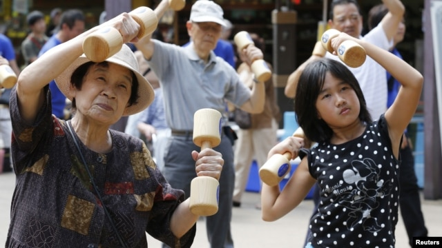 "A girl exercises with other people using wooden dumbbells during a health promotion event to mark Japan's ""Respect for the Aged Day"" at a temple in Tokyo on September 17, 2012."