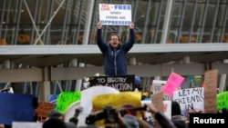 一名男子在紐約肯尼迪國際機場外對美國新移民禁令表示不滿(2017年1月31日)