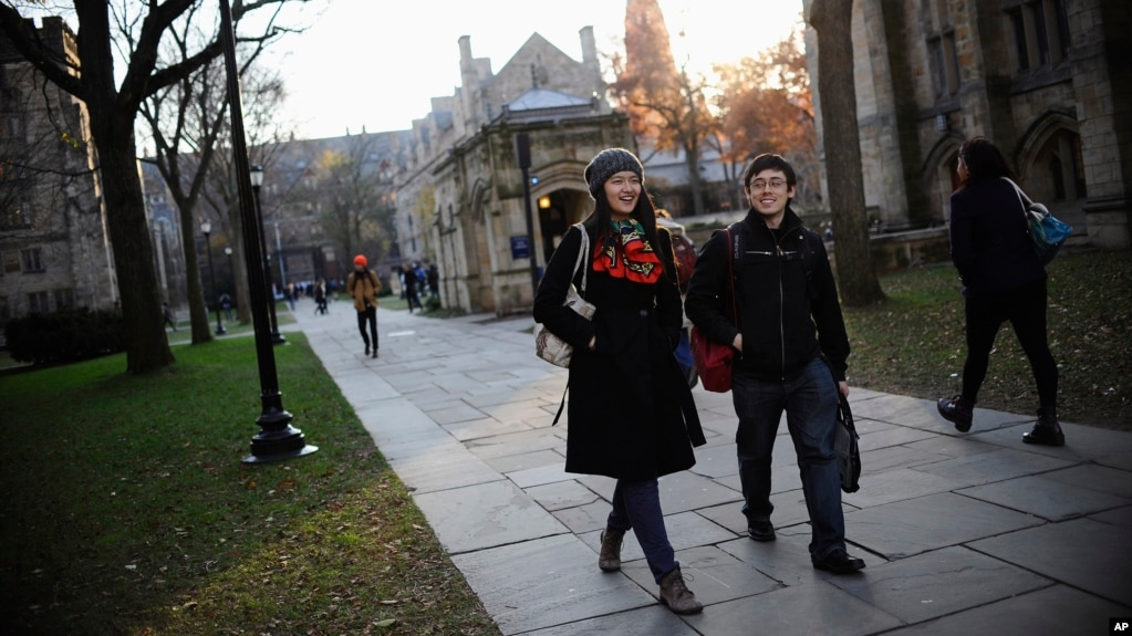 FILE - Yale University sophomore Yupei Guo, left, walks with friend Joseph Lachman on the school's campus in New Haven, Conn., In Nov. 20, 2014. With more undergraduates coming from overseas than ever, some Ivy League universities are reaching out in new ways to attract international students of more varied backgrounds -- and particularly from China, which sends more students to the U.S. than any other country.