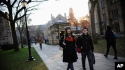 FILE - Yale University sophomore Yupei Guo, left, walks with friend Joseph Lachman on the school's campus in New Haven, Conn., In Nov. 20, 2014. With more undergraduates coming from overseas than ever, some Ivy League universities are reaching out in new