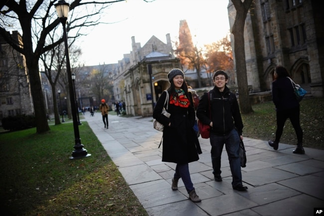 FILE - Yale University sophomore Yupei Guo, left, walks with friend Joseph Lachman on the school's campus in New Haven, Conn., In Nov. 20, 2014