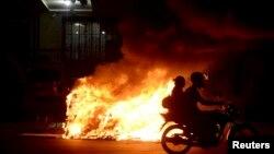 Pengendara sepeda motor melewati kobaran api di jalan ketika terjadi unjuk rasa menuntut kenaikan ongkos transportasi umum di Brazil.