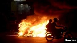 Una motocileta pasa frente a una fogata durante una protesta contra el alza de pasajes en el transporte, en Rio de Janeiro, Brasil.