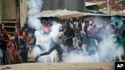 Supporters of Kenyan opposition leader and presidential candidate Raila Odinga throw back a tear gas canister at Kenyan security forces in the Mathare slum of Nairobi, Aug. 9, 2017.