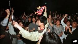 资料照片:在北约误炸中国驻南斯拉夫大使馆之后,北京学生在美国使馆外面焚烧美国国旗。(1999年5月8日)