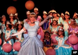 Local schoolgirls watch an actress dressed up as Disney character Cinderella perform at an event in Mumbai, India, 2012.