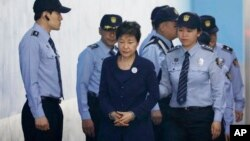 Former South Korean President Park Geun-hye, center, arrives for a court hearing in Seoul, South Korea, May 23, 2017. North Korea on Wednesday vowed to execute Park and her spy director, accusing them of planning to assassinate its supreme leadership.