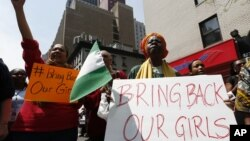 Activist Dr. Delois Blakely, right, is joined by others while chanting during a rally in front of the Nigerian consulate, May 10, 2014, in New York.