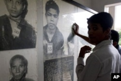 FILE -Cambodian men view portraits of Khmer Rouge's victims at Tuol Sleng genocide museum in Phnom Penh, Cambodia. (AP Photo)