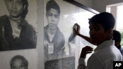 Cambodian men view portraits of Khmer Rouge's victims at Tuol Sleng genocide museum.