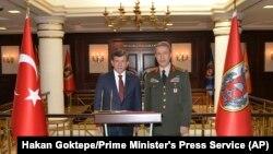 Perdana Menteri Turki Ahmet Davutoglu (kiri) didampingi oleh Kepala Staf Angkatan Bersenjata Turki Jenderal Hulusi Akar saat menyampaikan peryantaan terkait ledakan di Ankara, Turki (18/2).