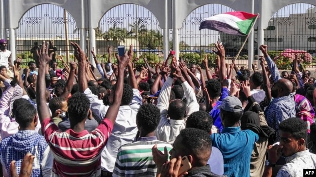 Sudanese protesters shout slogans in front of the military headquarters in the capital Khartoum, April 6, 2019.