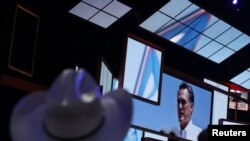Para delegasi melihat gambar capres AS Mitt Romney pada upacara pembukaan konvensi nasional partai Republik di Tampa, Florida, Senin (27/8). Romney dijadwalkan tiba di Tampa hari Selasa ini.