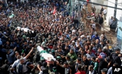 FILE - Palestinian mourners carry the bodies of two of the seven Hamas militants who were killed in an Israeli raid late Sunday, during their funerals in Khan Younis, southern Gaza Strip, Nov. 12, 2018.