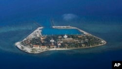 FILE - The Vietnamese-claimed Southwest Cay island in the Spratly island group is seen from a Philippine Air Force C-130 transport plane during the visit to the Philippine-claimed Thitu Island by Defense Secretary Delfin Lorenzana.