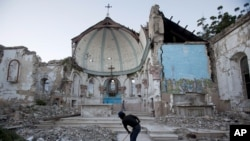 A man sweeps an exposed tiled area of the earthquake-damaged Santa Ana Catholic church, where he now lives, in Port-au-Prince, Haiti, January 12, 2013.