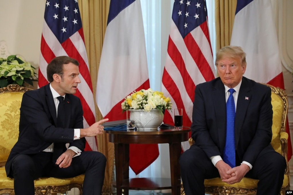 U.S. President Donald Trump (R) listens as French President Emmanuel Macron speaks during their meeting at Winfield House, London.