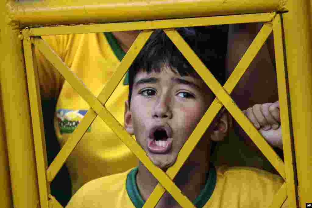 A young soccer fan shouts from outside the stadium fence asking to enter Brazil's soccer team training session in Fortaleza, Brazil, July 3, 2014.