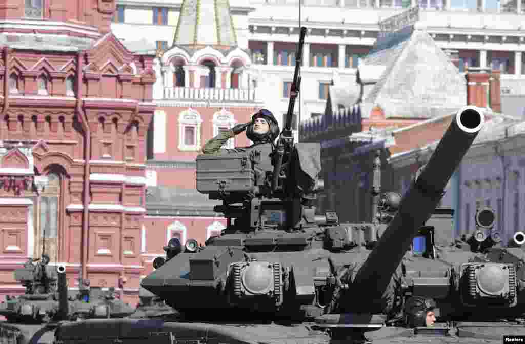 A Russian serviceman aboard a tank salutes during the Victory Day parade in Moscow's Red Square.