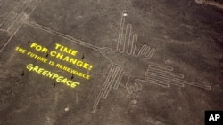 "Greenpeace activists stand next to massive letters delivering the message ""Time for Change: The Future is Renewable"" next to the hummingbird geoglyph in Nazca in Peru, Dec. 8, 2014."