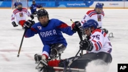 Czech Republic's Jiri Raul keeps the puck from South Korea's Choi Kwang Hyouk, left, during a preliminary Ice Hockey match of the 2018 Winter Paralympics held in Guangneung, South Korea, March 11, 2018.