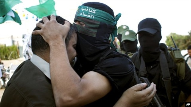 A masked Hamas militant kisses freed Palestinian prisoner Mahawish al Qadi, left, who was involved in organizing the abduction of Israeli soldier Gilad Schalit, in Rafah, southern Gaza Strip, Oct. 19, 2011.