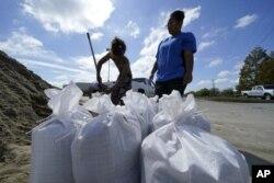 Stephanie Verrett, Louisiana eyaletinin Houma kasabasındaki evini su baskınından korumak için kum torbaları hazırlıyor.