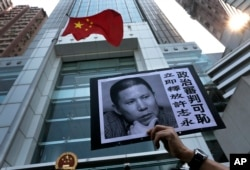 FILE - A placard with a photo of Xu Zhiyong is raised by a demonstrator protesting against a Chinese court's decision to sentence him in prison outside the Chinese liaison office in Hong Kong, Jan. 27, 2014.