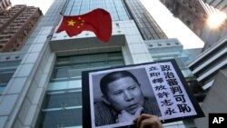 A placard with a photo of legal scholar Xu Zhiyong is raised by a demonstrator protesting against a Chinese court's decision to sentence him in prison outside the Chinese liaison office in Hong Kong, Jan. 27, 2014.