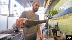 Barmen u restoranu Fish & Oyster sipa vino za mušterije u Solt Lejk Sitiju.