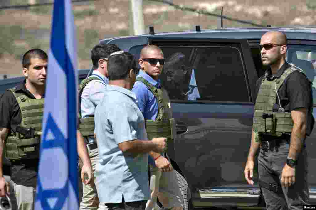 Israeli Prime Minister Benjamin Netanyahu steps out of his car as bodyguards surround him while attending a meeting at an army base near the West Bank city of Nablus, Oct. 6, 2015.