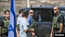 Thủ tướng Israel Benjamin Netanyahu bước ra khỏi xe hơi trong lúc các vệ sĩ đứng canh gác gần thành phố Bờ Tây Nablus, ngày 6/10/2015.