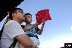 Foto yang diambil pada 6 September 2018 menunjukkan seorang pria menggendong anaknya di sebuah taman di Beijing. China bersiap untuk menghapus kebijakan dua anaknya.