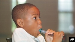 FILE - Alexander McBride, 8, who has asthma, exhales into a peak flow meter in Severna Park, Maryland, Aug. 13, 1998.