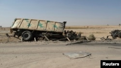 FILE - A burnt vehicle belonging to the Iraqi security forces is seen on the outskirt of Haditha, northwest of Baghdad August 26, 2014. On Monday, Jan. 4, 2016, IS militants attacked Iraqi troops and allied tribal fighters outside Haditha, killing at least 11 and wounding dozens.