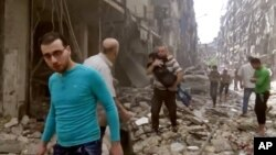 In this image made from video and posted online from Validated UGC, a man carries a child after airstrikes hit Aleppo, Syria, April 28, 2016.