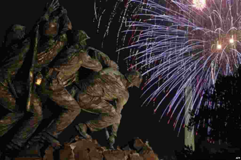 The United States Marine Corps War Memorial, better known as the Iwo Jima Memorial, is seen in Arlington, Va., Monday July 4, 2011, as fireworks burst over Washington, during the annual Fourth of July display. (AP Photo/Carolyn Kaster)