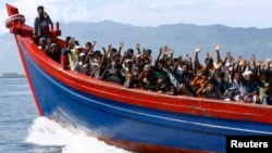 Ethnic Rohingya refugees from Burma wave as they are transported by a wooden boat to a temporary shelter in Krueng Raya in Aceh Besar. (File photo)
