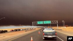 Smoke from the Camp Fire, burning in the Feather River Canyon near Paradise, Calif., darkens the sky as seen from Highway 99 near Marysville, Calif., Nov. 8, 2018.