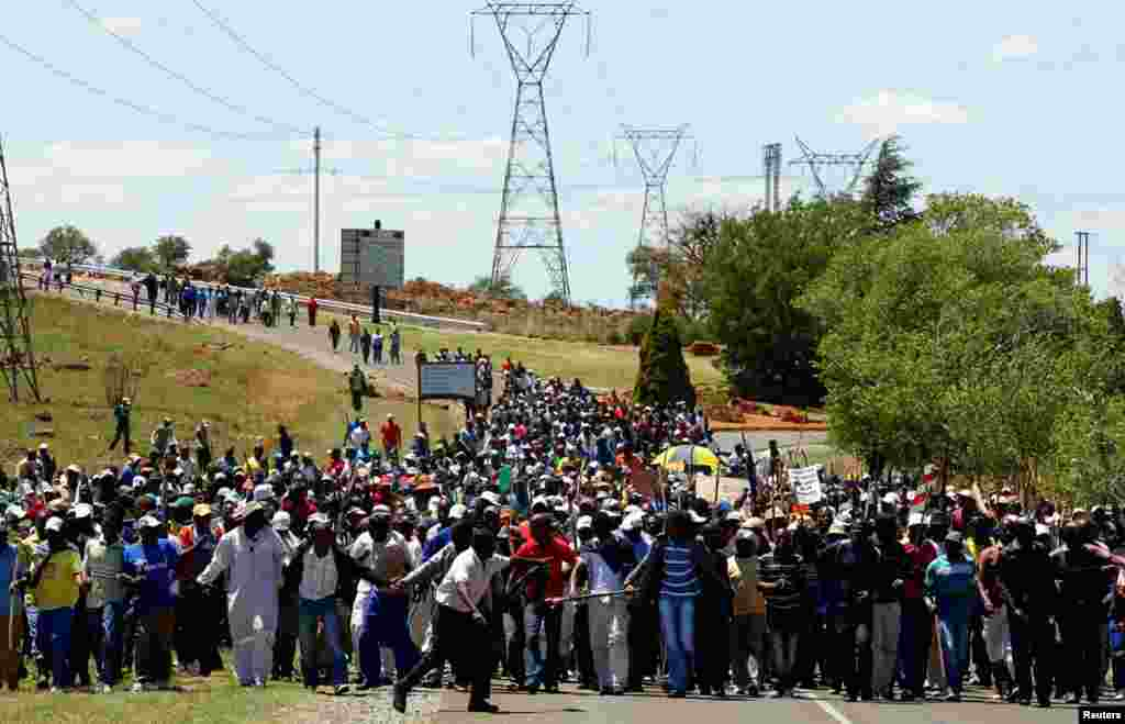 Striking miners march to meet some of the management team at the AngloGold Ashanti mine in Carletonville, South Africa, October 18, 2012.