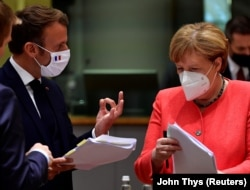 German Chancellor Angela Merkel looks into a document as France's President Emmanuel Macron gestures during the first face-to-face EU summit since the coronavirus disease (COVID-19) outbreak, in Brussels, Belgium July 20, 2020.