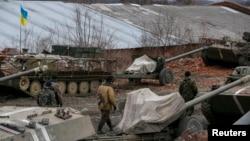 Binh sĩ Ukraine bên cạnh các xe quân sự và vũ khí được rút ra khỏi khu vực Horlivka, gần Druzhkivka, miền đông Ukraine, ngày 28/2/2015.