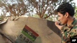 A Libyan rebel looks at the tail of a rebel MIG-23 jet in Benghazi on June 26, 2011 at the site where the jet crashed after it was shot down on March 19, 2011.